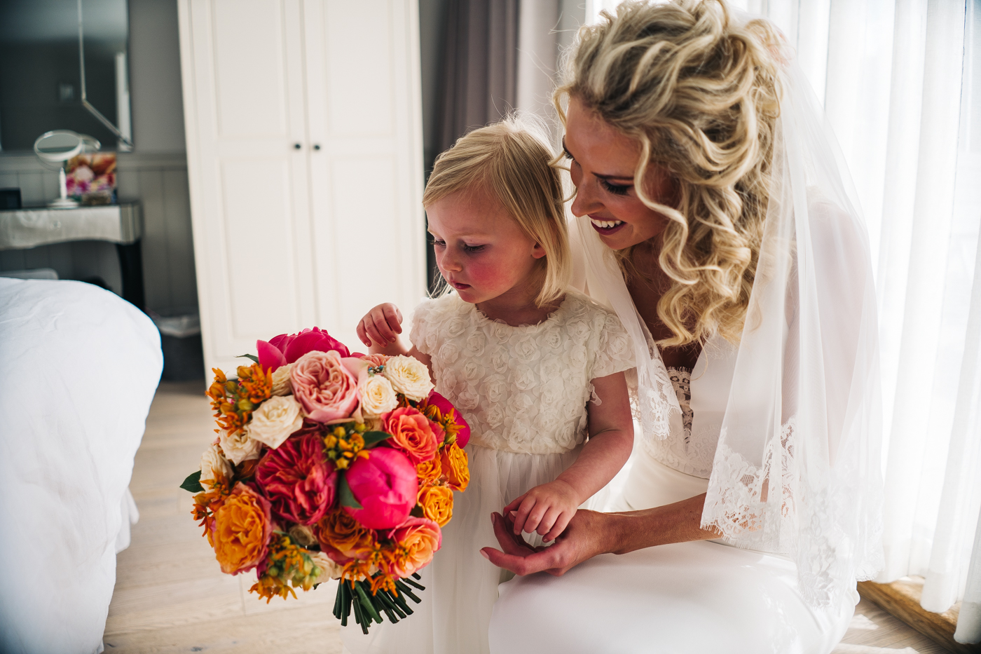 a bride and her flower girl cuddle and look at her bouquet. photo by sally t photography, wedding at ever after, tavistock, devon photographer