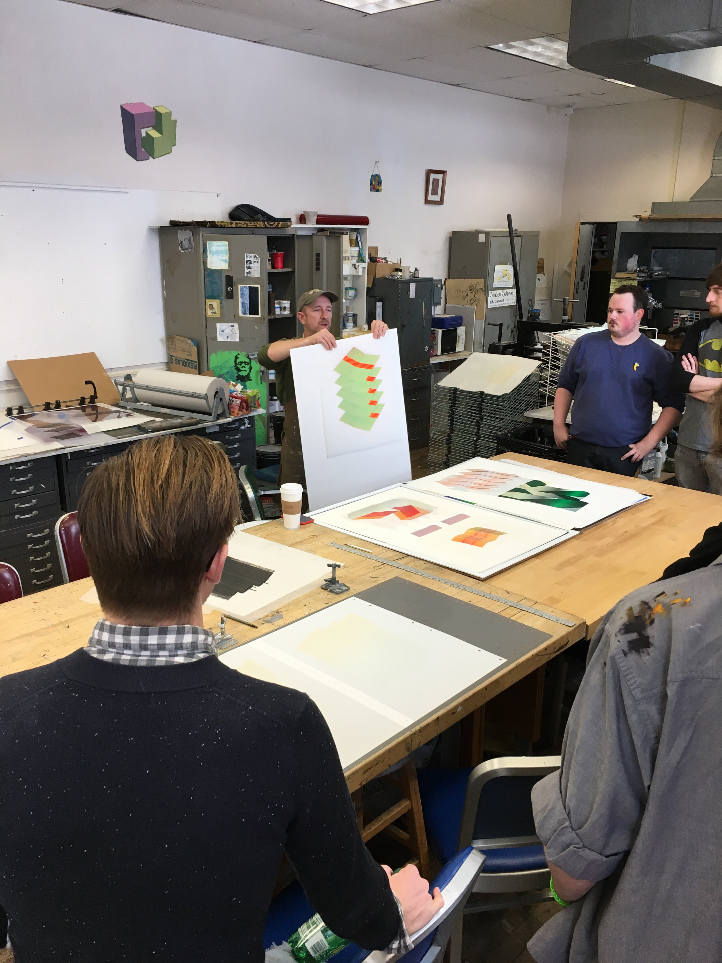 Visiting artist Jeffrey Dell sharing prints with students.