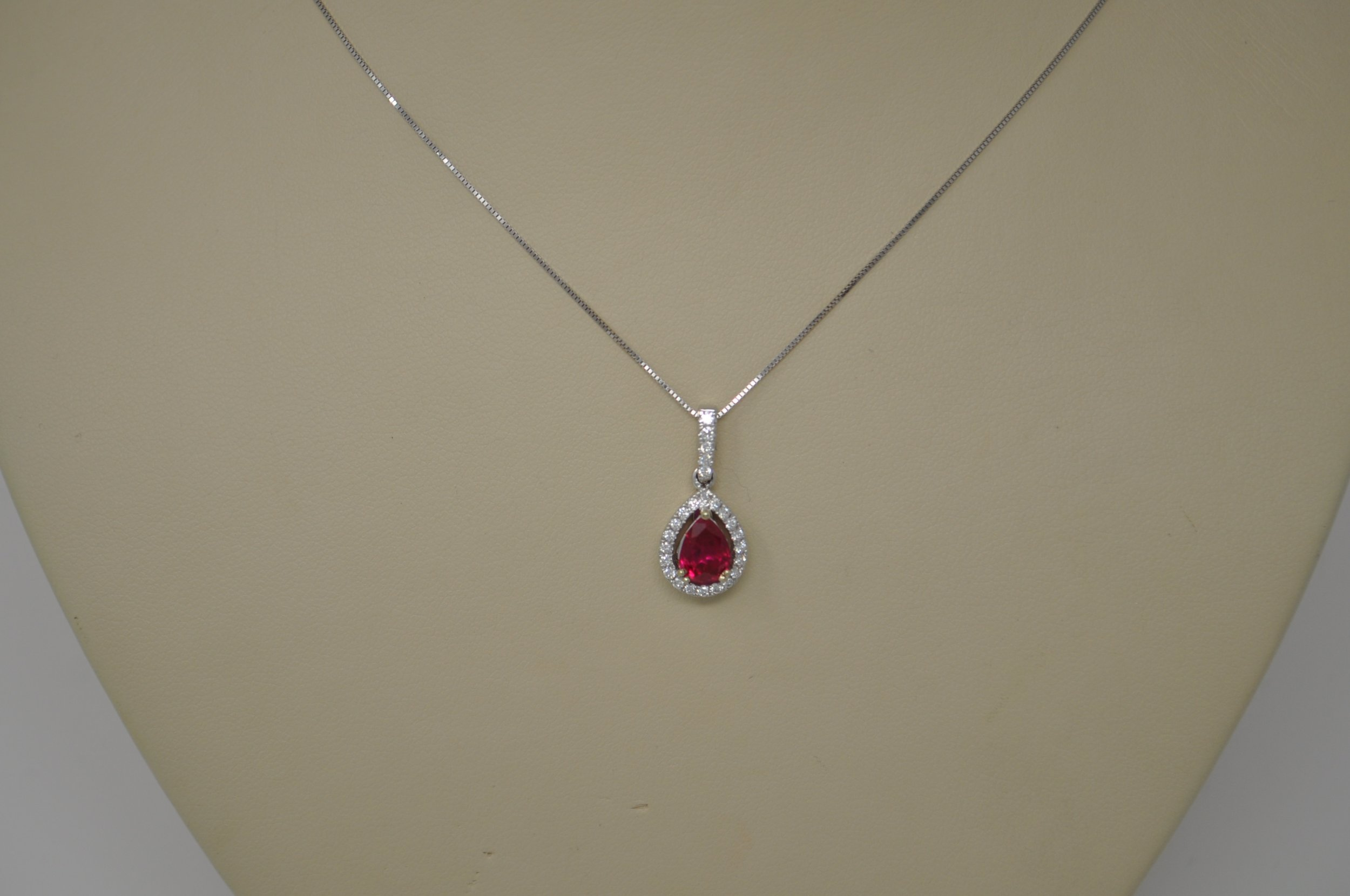Ruby Pendant-stunning ruby and diamond pendant features a 1.09 ctw pear-cut lab-created ruby stone flanked by a halo of 25 diamonds on a 17 inch box chain. retail $1210.00