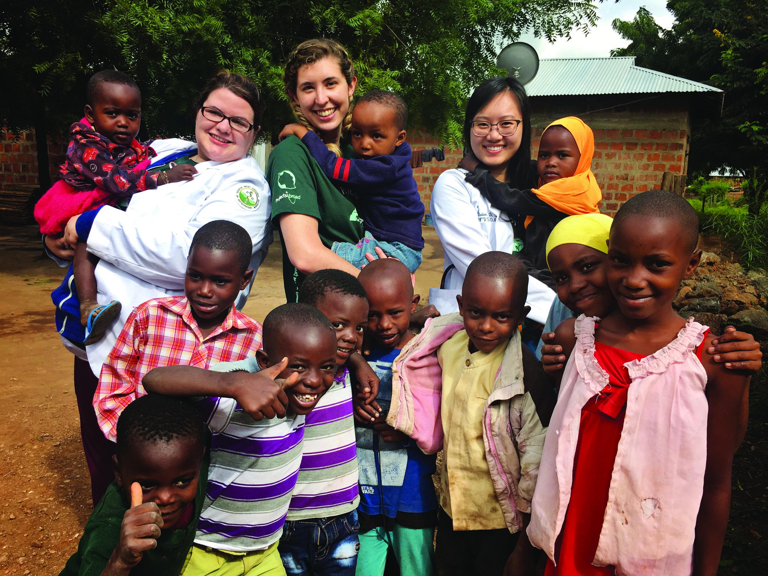 Emily Watson, Kate Warren, and Vivian To with village children.