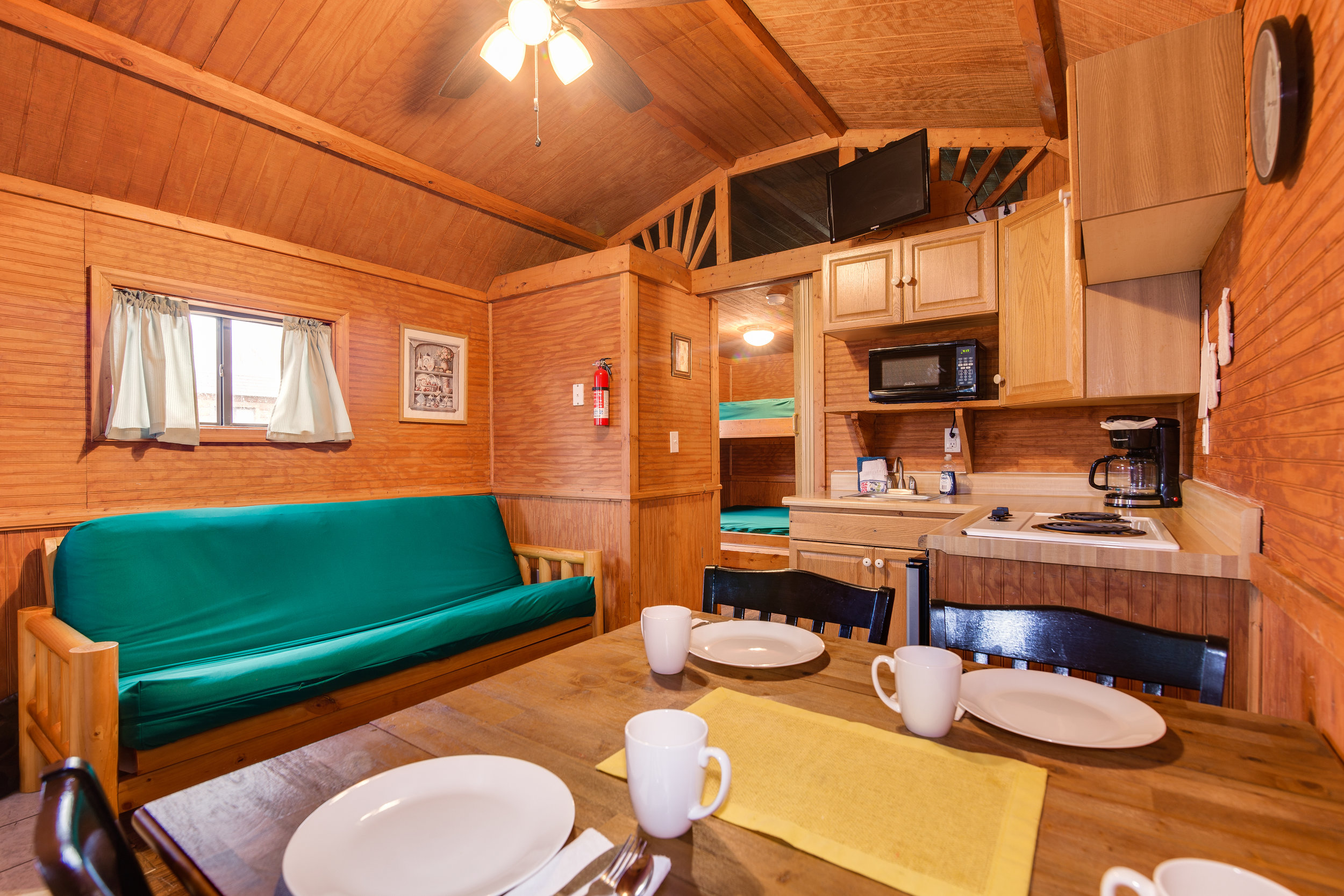 The deluxe cabins feature a futon in the living space, a table and chairs that seat four, and a partial kitchen (pictured). Kitchen linens, pots and pans, glasses, silverware, and dishes are included. There is also a television with campground cable.