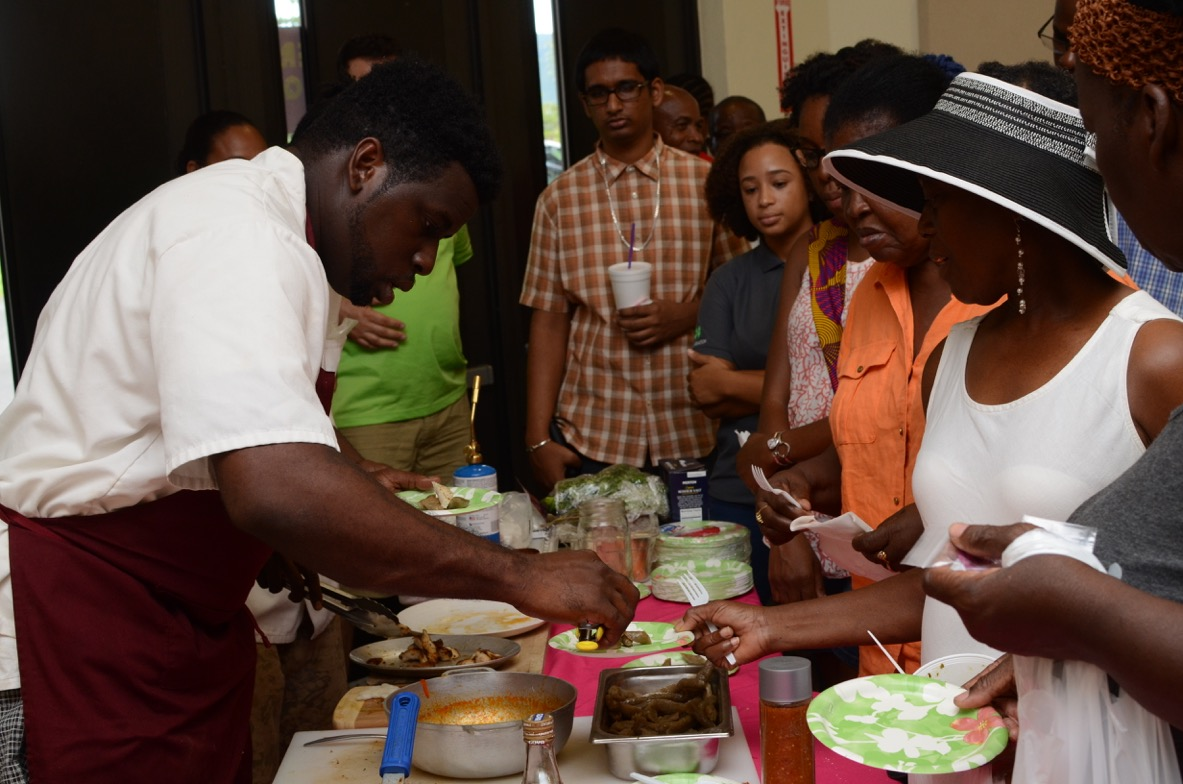 Chef Byron serves lion fish and dumplings to some hungry customers at UVI World Food Day.