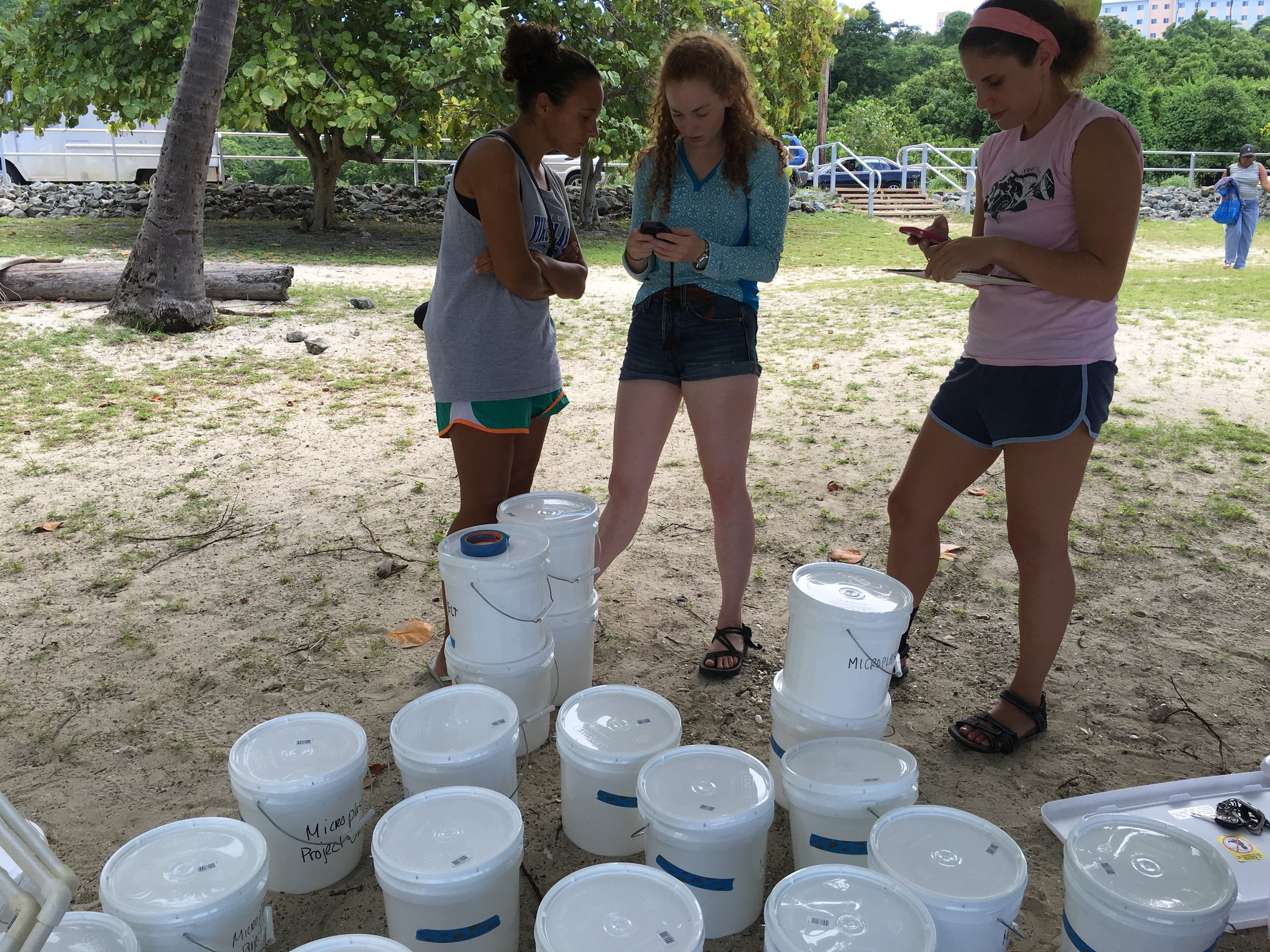 Danie (far right) and members of her team are prepping and organizing for sampling. The buckets are labeled with quadrant and transect number. At center is Allie Durdall, a UVI graduate student on St. Croix with a focus on the Salt Pond ecosystem and left, Mara Duke, who is quantifying zooplankton in Brewers Bay and the microplastics found in the zooplankton samples.