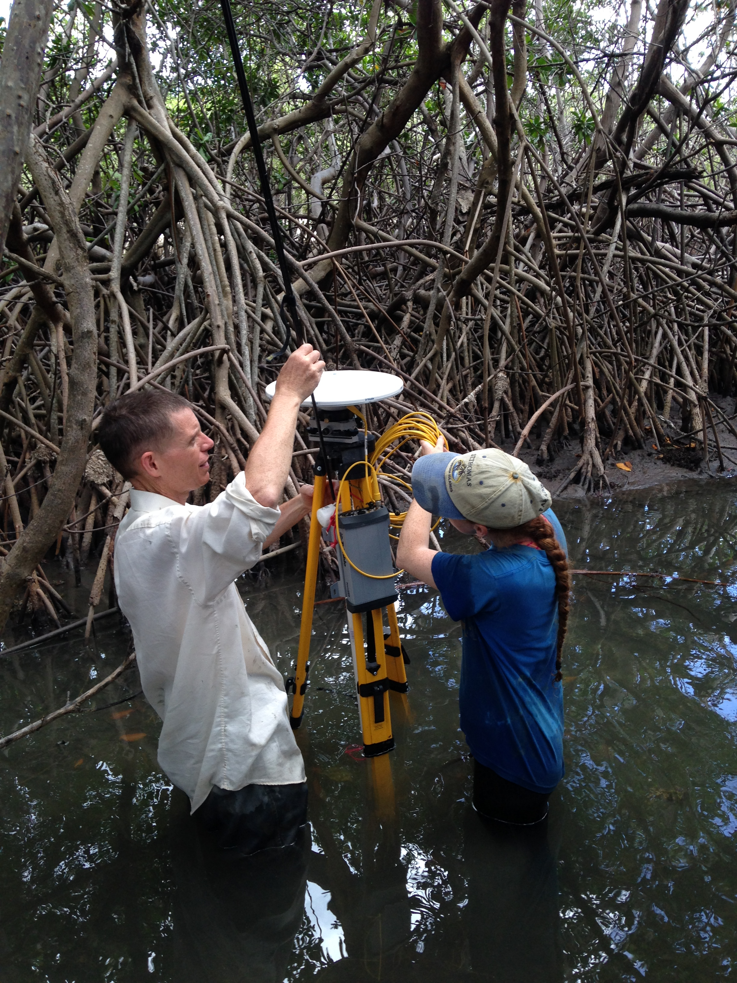 Allie Durdall and Andrew Reeve, Ph.D.setting up the GPS equipment over the groundwater wells to get precise elevations which are needed to understand groundwater movement.