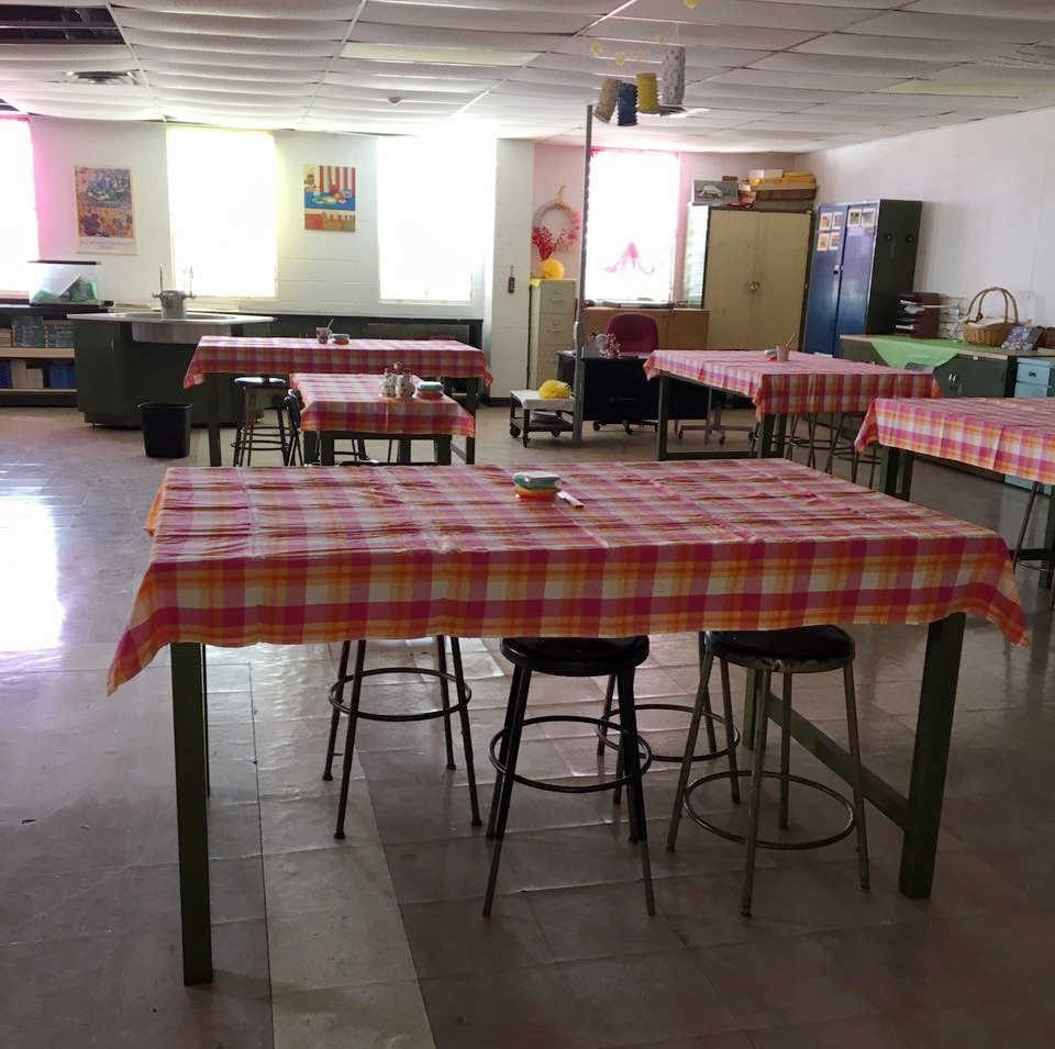 """By early October, Ms. Ravalier had completed the entry to her classroom """"Science Café,"""" complete with artwork on the door and cheerful tablecloths – though ceiling tiles still displayed evidence of Hurricanes Irma and Maria.  Photo by Michealrose Ravalier."""