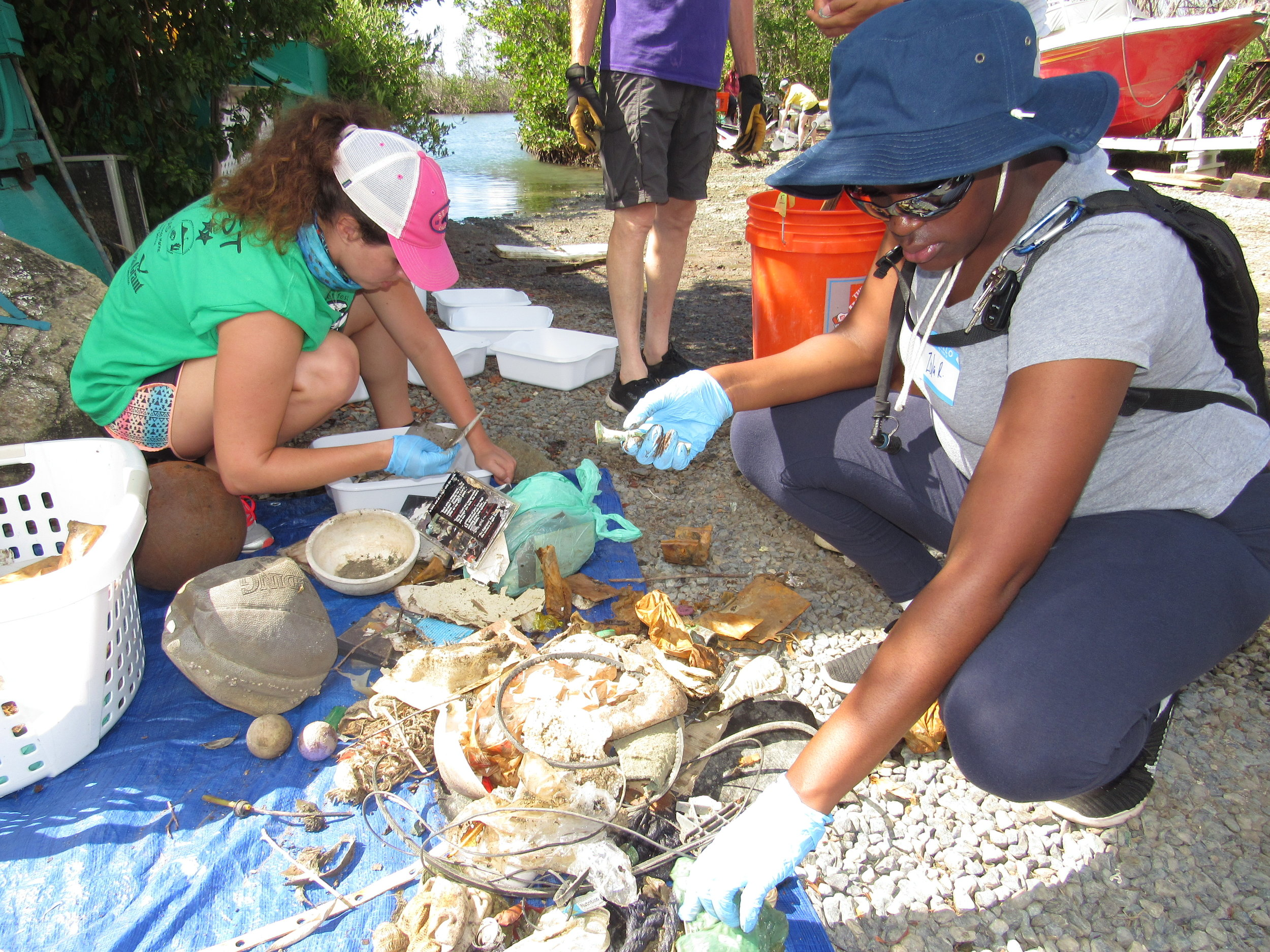 University of the Virgin Islands Masters of Marine & Environmental Science student volunteers, Danielle Lasseigne and Zola Roper, sort and count marine debris items at the Great Mangrove Cleanup.  Photo credit: Jarvon Stout