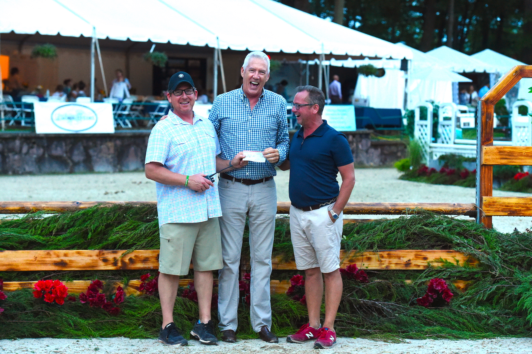 Tucker Ericson and Michael Dowling present a check on behalf of Monmouth at the Team to the Equestrian Aid Foundation board member Scot Evans.Photo by Anne Gittins Photography