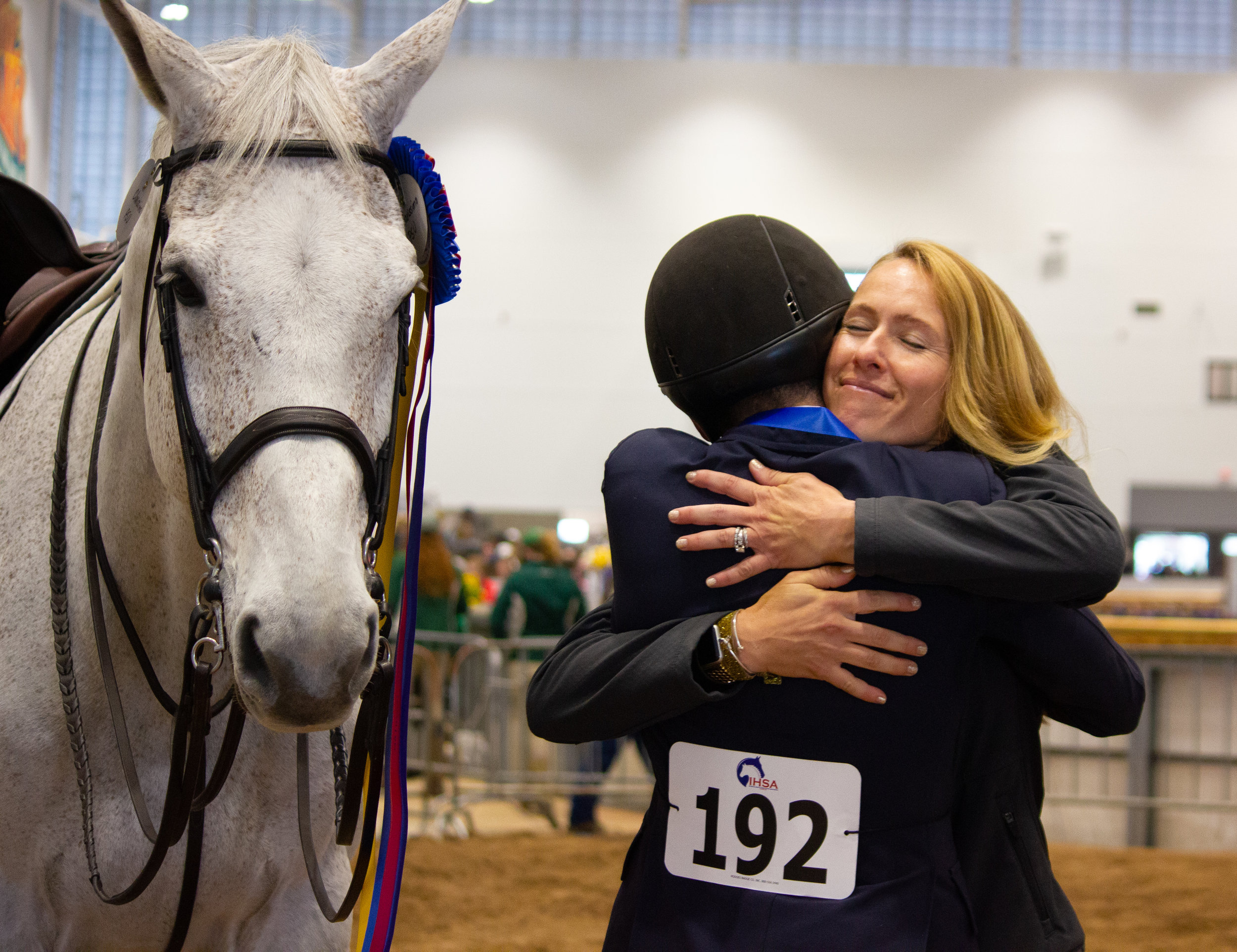 Adam Edgar gets a hug from SCAD coach Ashley Henry as Clarissimo, owned by Hollins University, looks on. Photo by Ellyn Narodowy