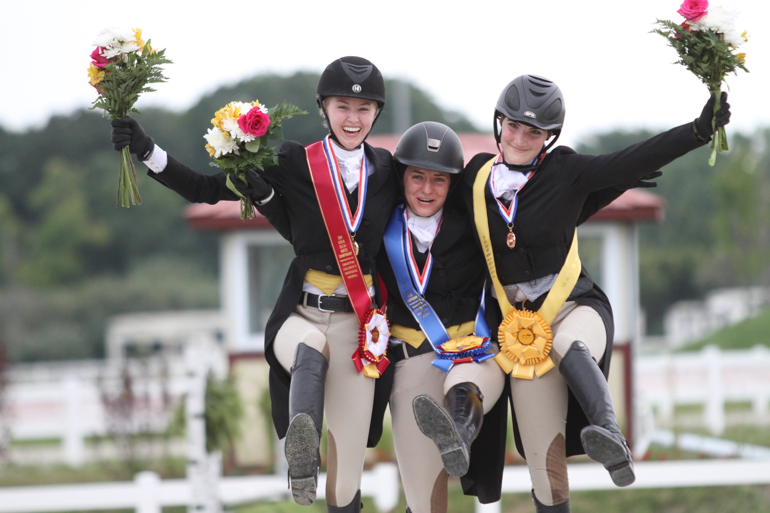 Silver medalist Grace Griffin, gold medalist Dayna Pochron and bronze medalist Lily Forney celebrate atop the podium as the top individuals in the Children's Hunter Individual Championship. Photo: EQ Media/USHJA