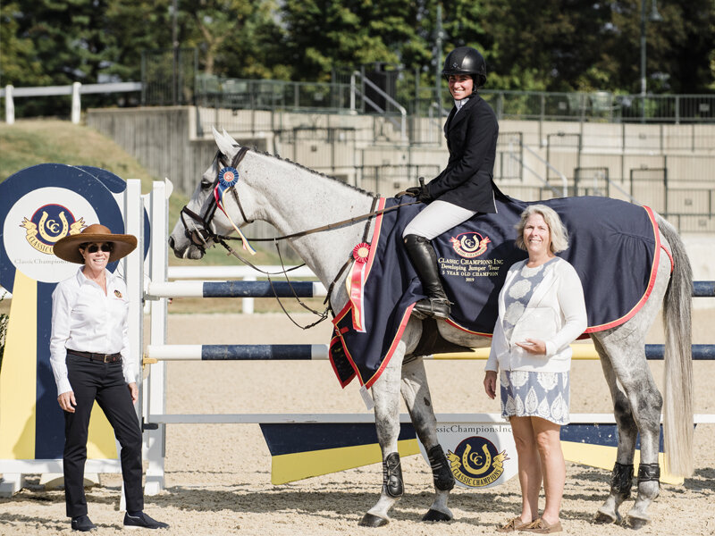 Cynthia Hampton presenting the champion ribbon and Classic Champions Award of Distinction to Jennifer Waxman and Out Of The Blue SCF owned by Lisa Lourie for the 5-year-old division. Photo By EQ Media
