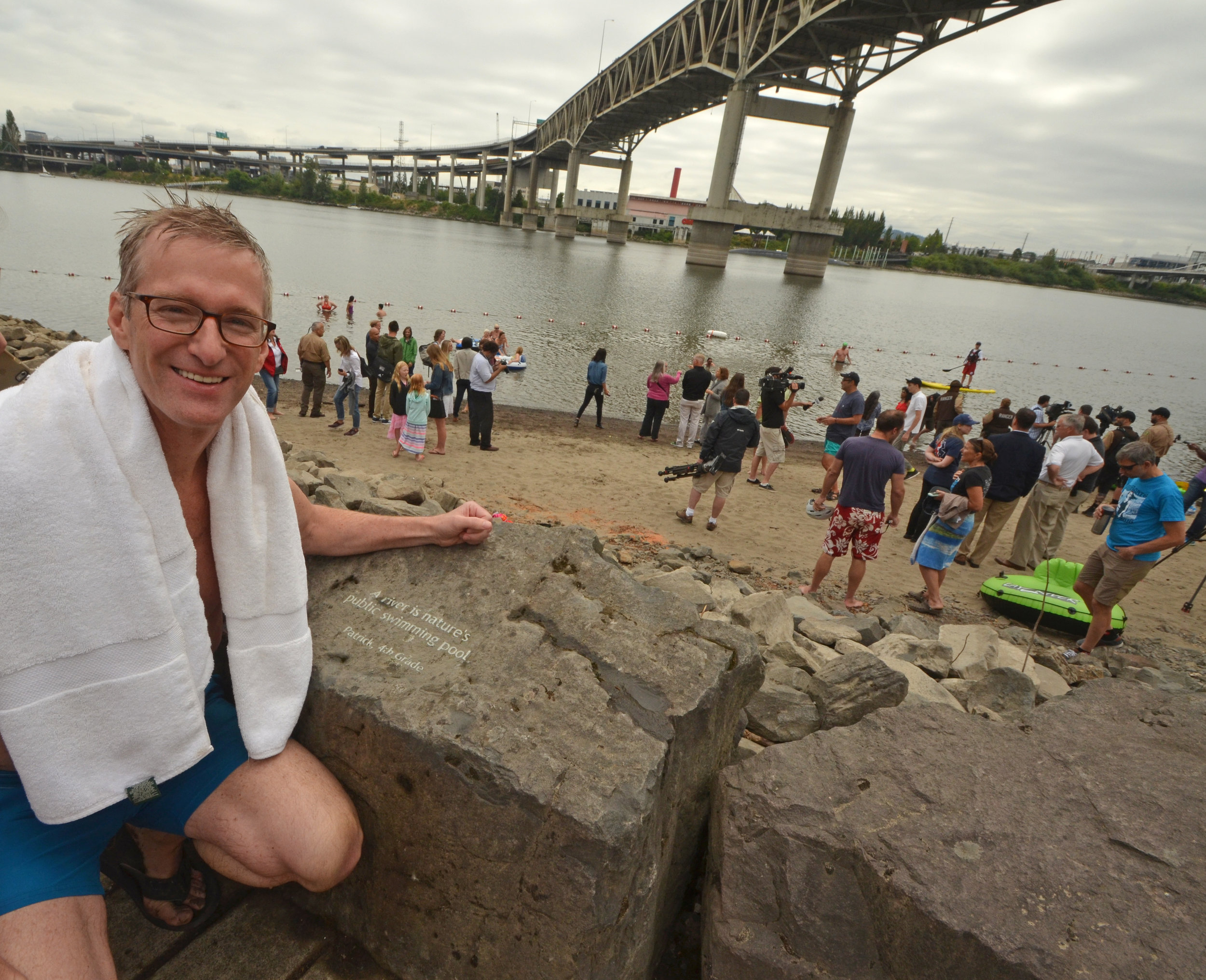 Mayor Ted Wheeler beside Honoring Our Rivers student poem at Poet's Beach.