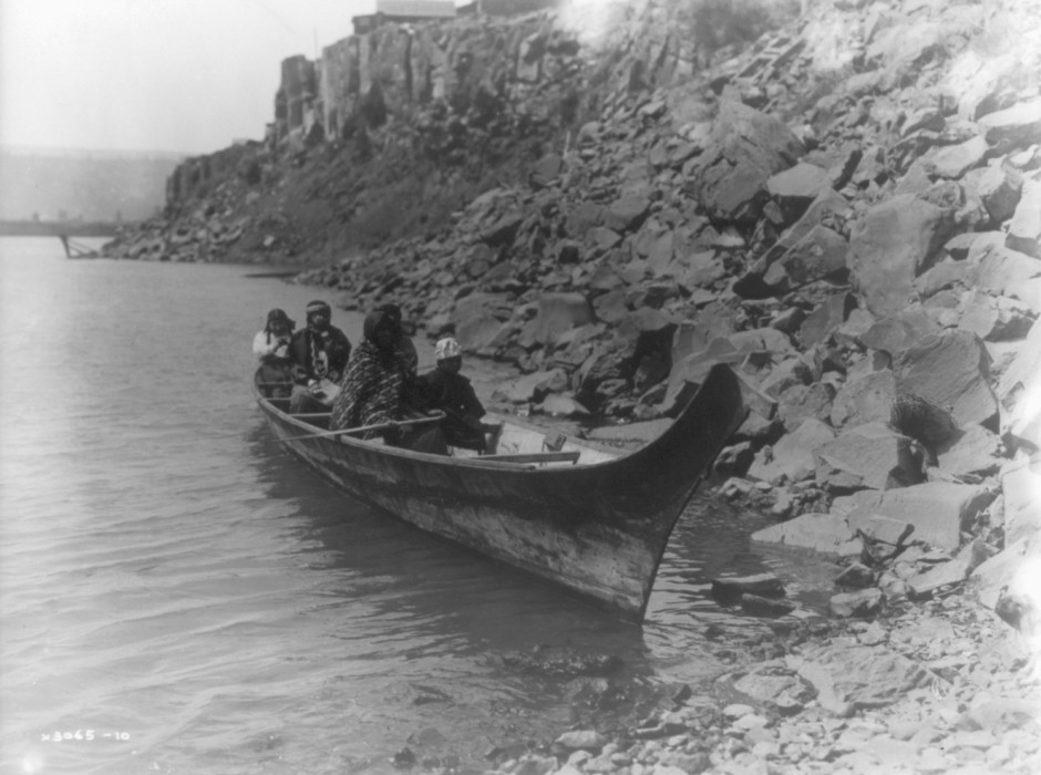 """Several Wishram Indians travel along the Columbia River in a raised-prow, Chinook-style canoe in this undated photo."" LIBRARY OF CONGRESS, #3A47171U /  OPB"