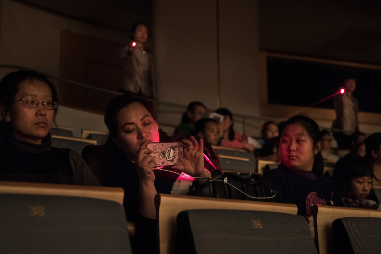 Ushers aiming lasers at a patron using a cellphone at the National Center for the Performing Arts in Beijing.   Credit: Gilles Sabrie for The New York Times