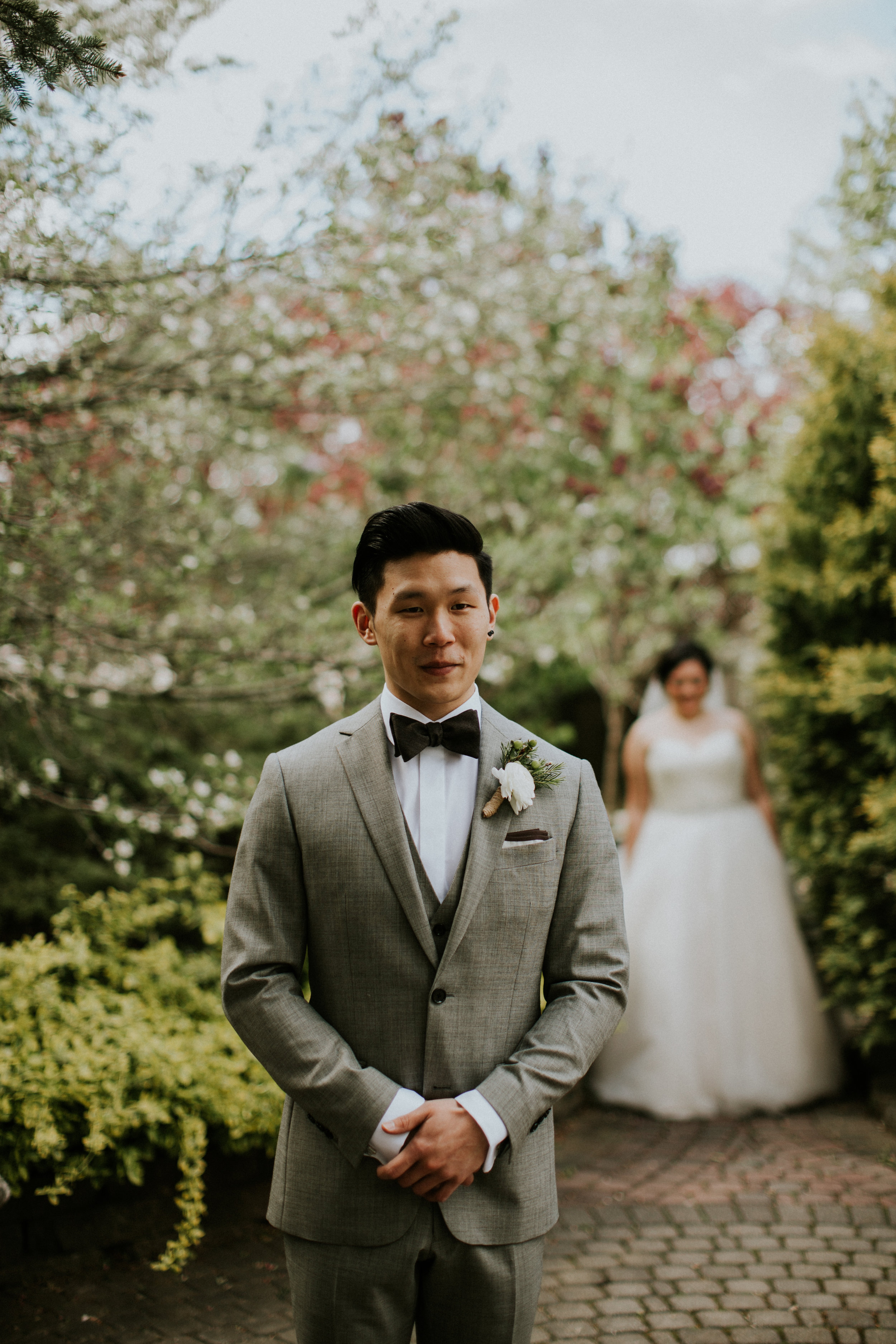 groom anxiously awaiting seeing bride for the first time during outdoor first look