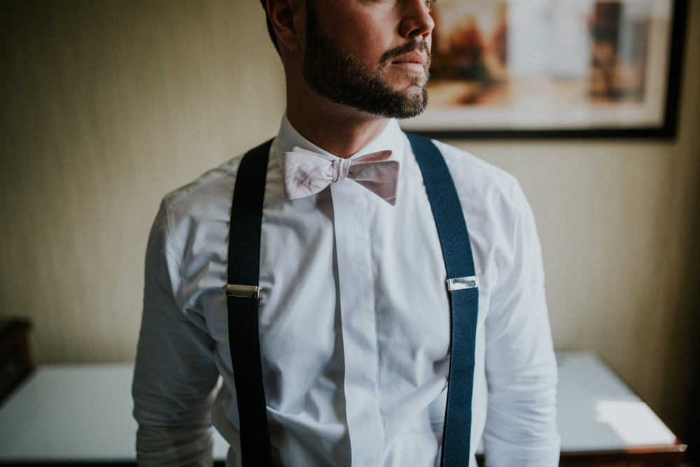 portrait of groom putting on bowtie and suspenders