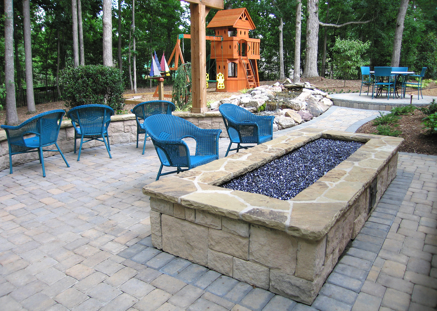 Ribbon fire feature, hardscape walkways and patio, waterfall and jungle gym playground