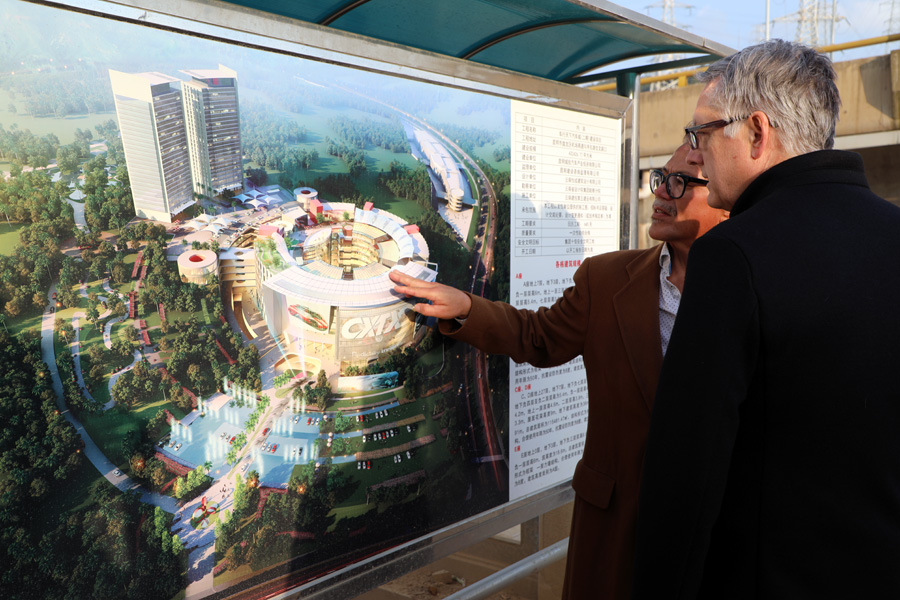 Windom Kimsey, FAIA, right, reviews a rendering of CXTX Auto City with motocross racing legend, Chuck Sun.