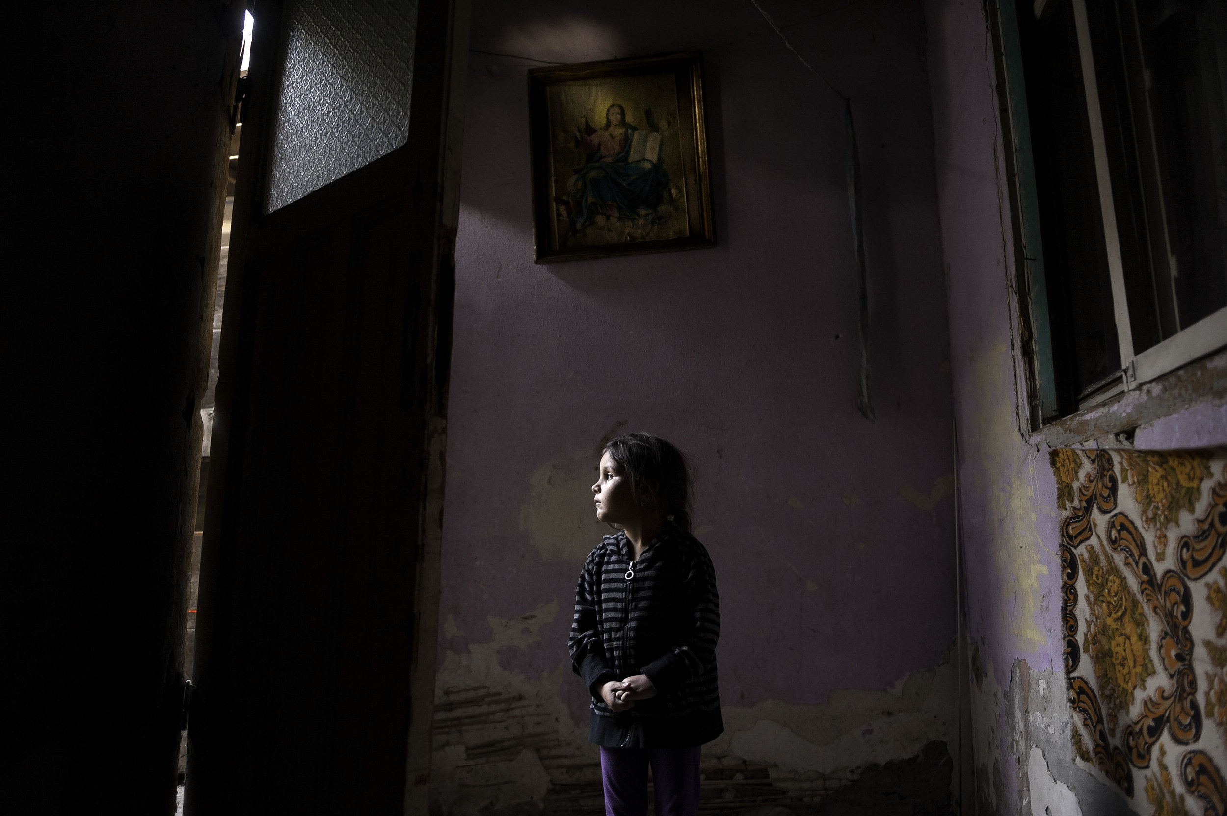 HOPING FOR A MIRACLE - Four-year-old Ana-Maria Tudor stands in the light of her doorway in Bucharest, Romania, hoping for a miracle as her family faces eviction from the only home they have ever known. Her father developed an infection following recent gallbladder surgery that has left him unable to work. The one room they live in has no bathroom or running water.