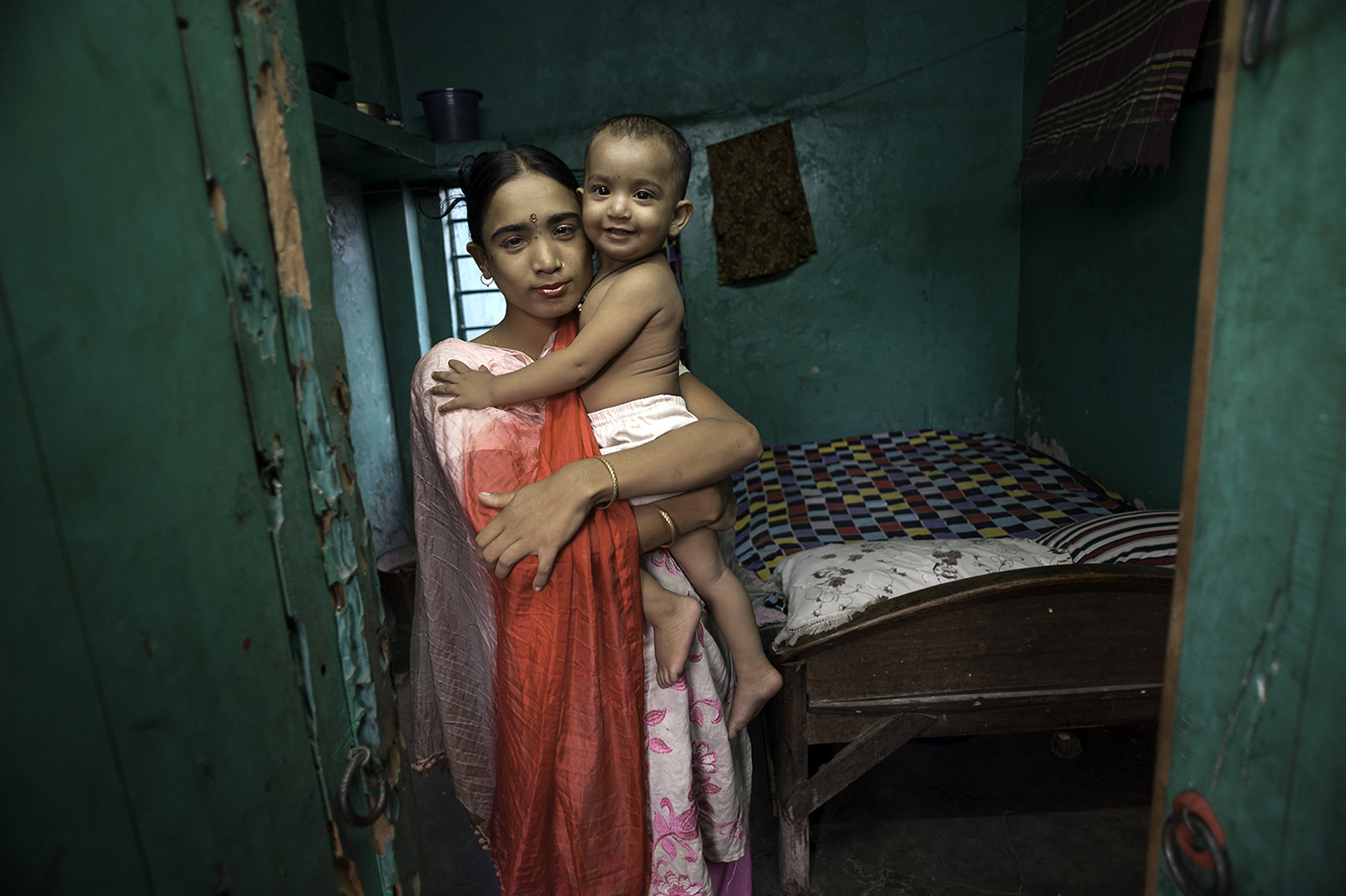 THE CYCLE CONTINUES - Labone, 27, takes a moment to hold her young daughter Nupur, 1, who was fathered by a client, before she has to return to her evening's work in a brothel in Jessore, Bangladesh. Most children born into the sex trade follow the same cycle of abuse as their mothers. With more than half of its population living below the poverty line, Bangladesh remains one of the poorest countries in the world