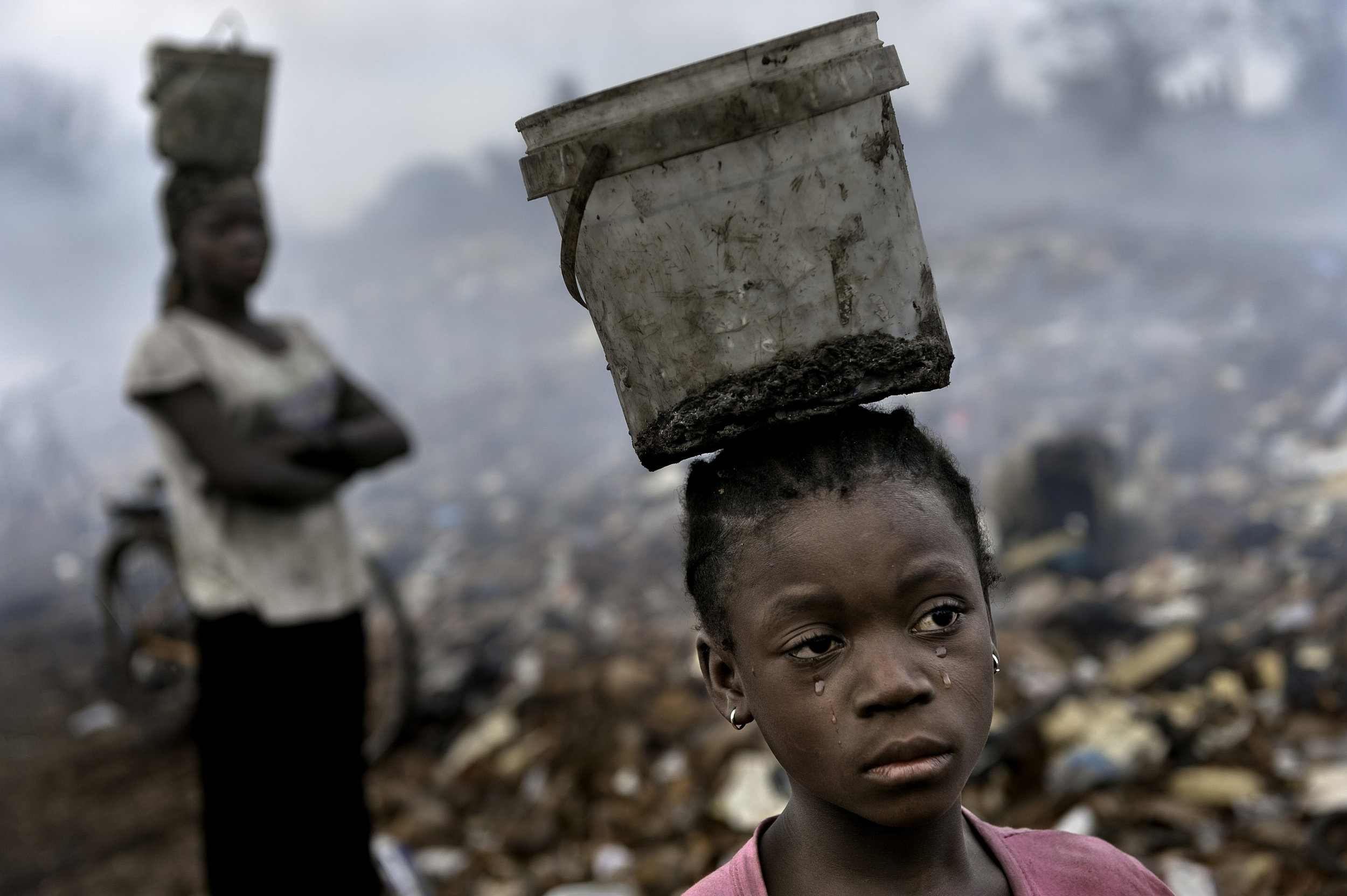 WORKING TO SURVIVE - In an e-waste dump that kills nearly everything that it touches, Fati, 8, works with other children searching through hazardous waste in hopes of finding whatever she can to exchange for pennies in order to survive. While balancing a bucket on her head with the little metal she has found, tears stream down her face as the result of the pain that comes with the malaria she contracted some years ago. This is work she must do to survive.