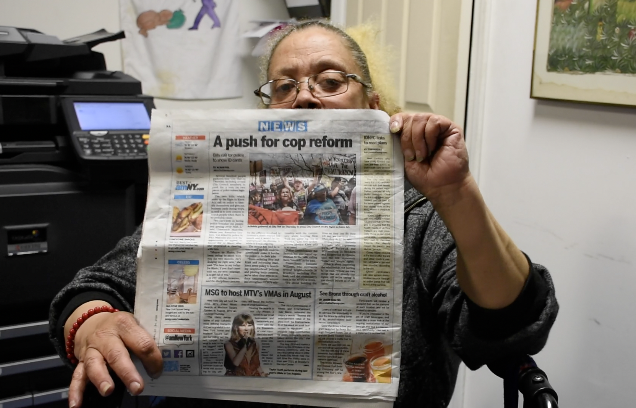 Picture the Homeless member Darlene Bryant holds up an article about a rally Picture the Homeless held in April.