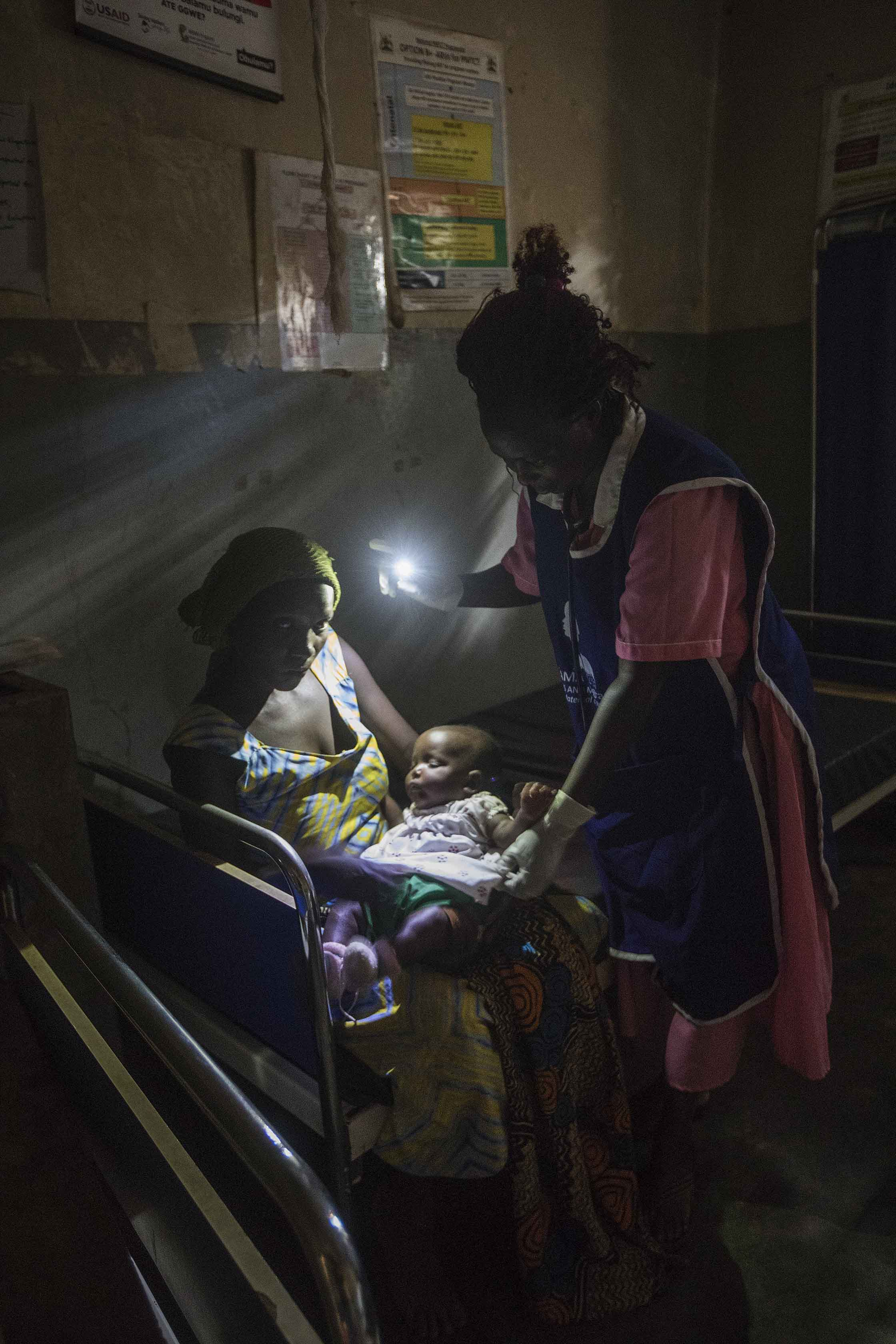 A midwife examining a child using a light from her cell phone