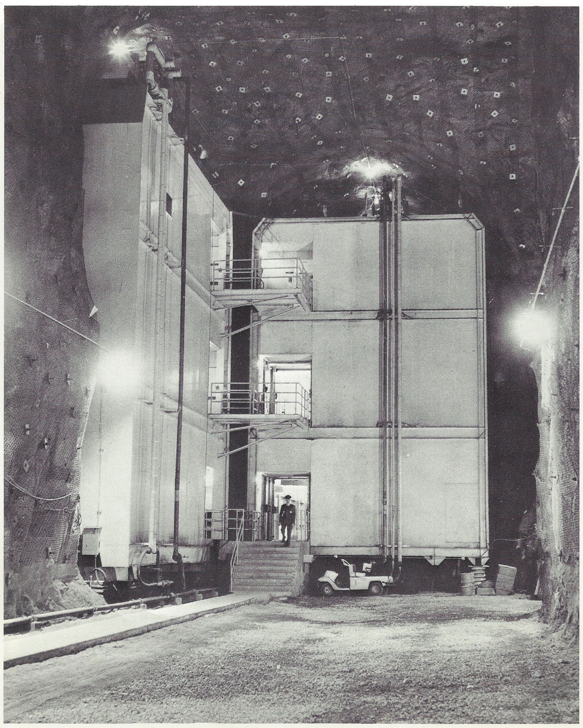 "Caption: ""These are two of the eleven buildings in the NORAD complex. While it possible to pass from one building to another through vestibules, the structures do not touch one another, nor do they touch the ceilings or walls of their granite cave. All the buildings are mounted on huge steel springs to protect the people and electronic equipment from shock waves."""