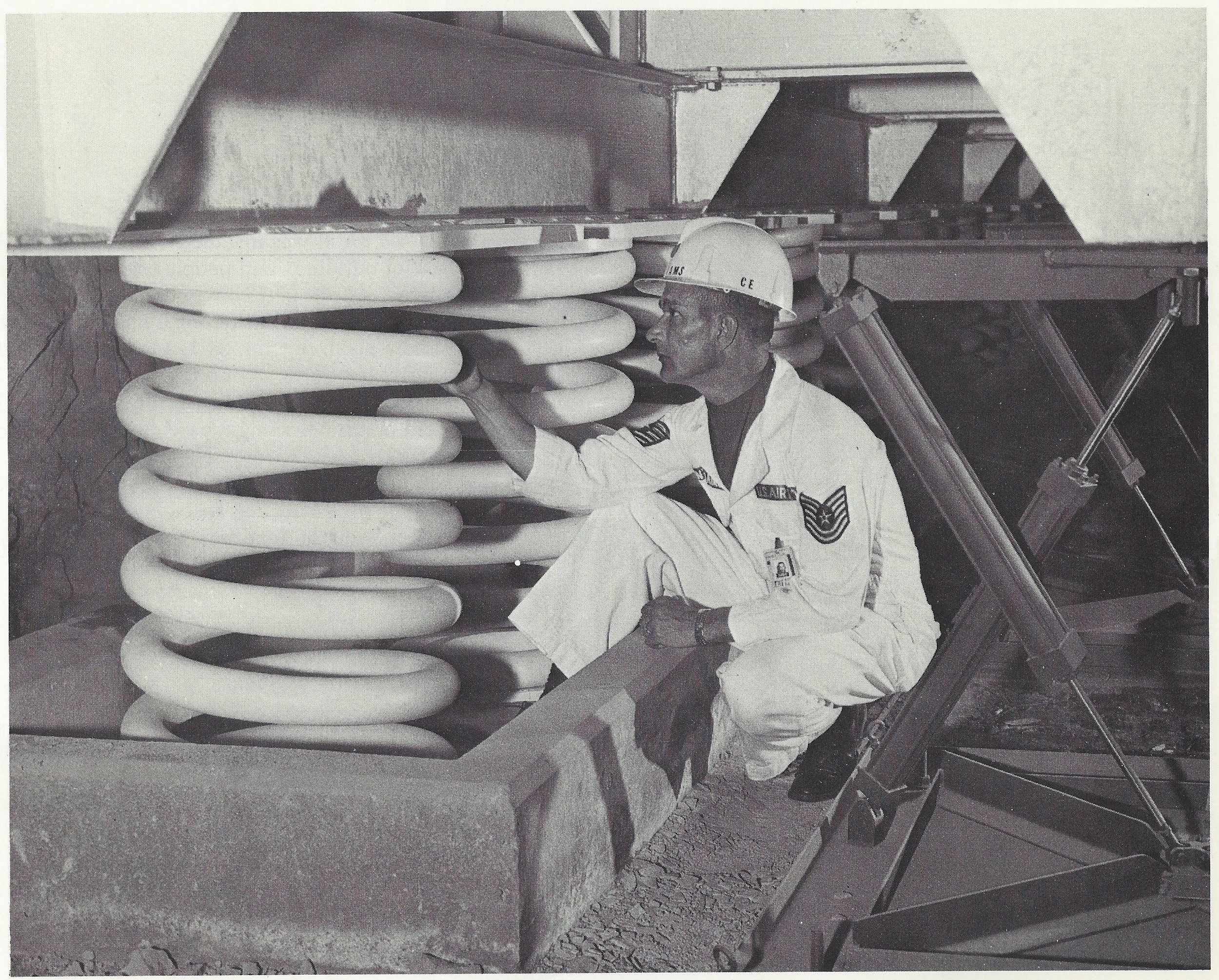 """Caption: """"CALLED FOR DEFENSE- Rows of mammoth springs made from three-inch diameter steel support the NORAD buildings. More than 900 of the springs, weighing 1,000 pounds eaach, cushion the buildings and their contents against jarring nuclear blasts or earthquakes. Working with the springs are the hydraulic dampers seen in the row at right. Like automobile shock absorbers, the dampers would reduce oscillations caused by a shock wave."""""""