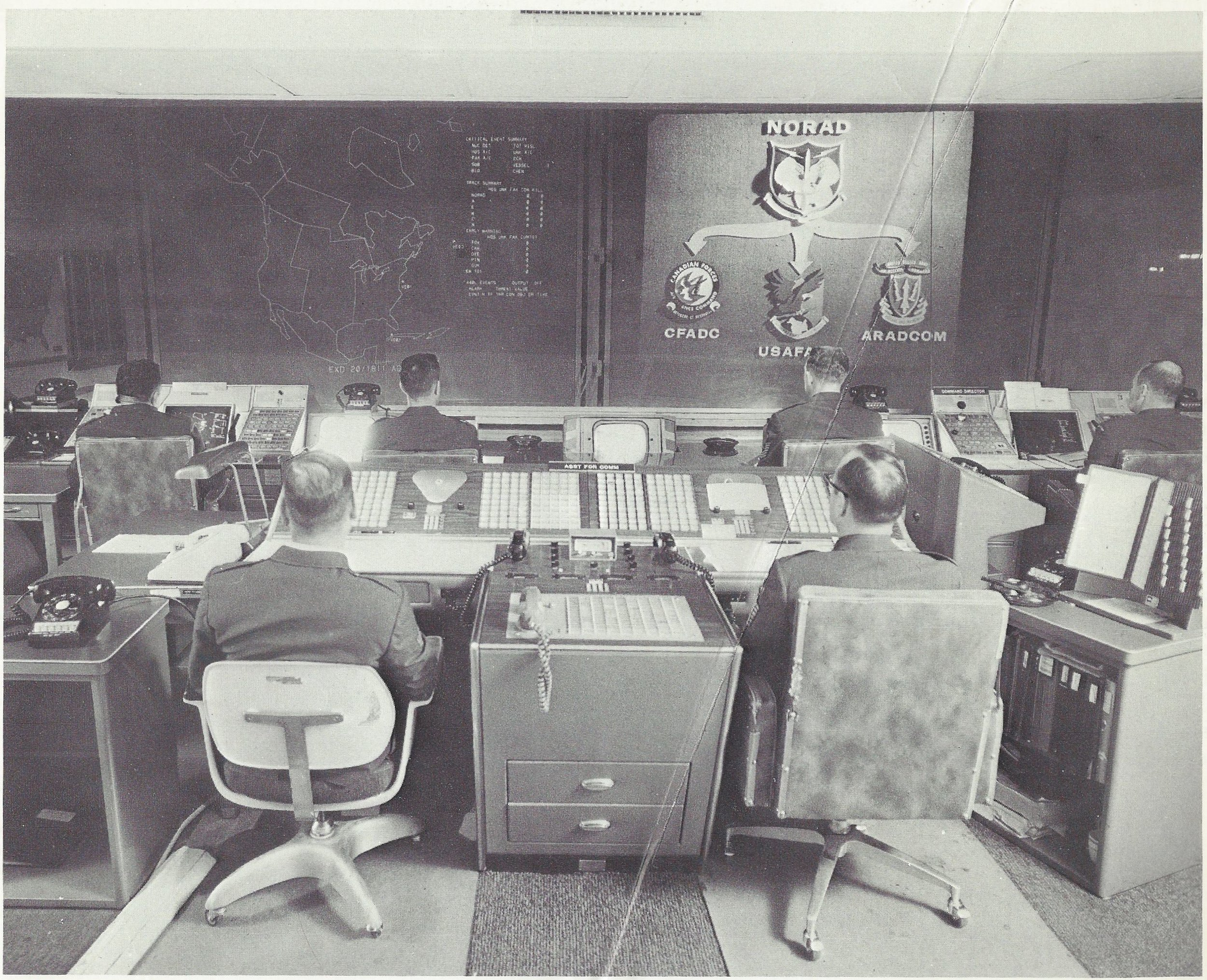 "Caption: ""AIR DEFENSE WATCH - These display screens would display signs of air attack against Canada and the United States. By pushing buttons, the NORAD battle staff members can take an electronic look at the tracks of space satellites or aircraft, which are chartered on the display by computers This is the nerve center which would give the first warning of attack, and the command post from which NORAD battle commanders would direct the defensive air battle."""