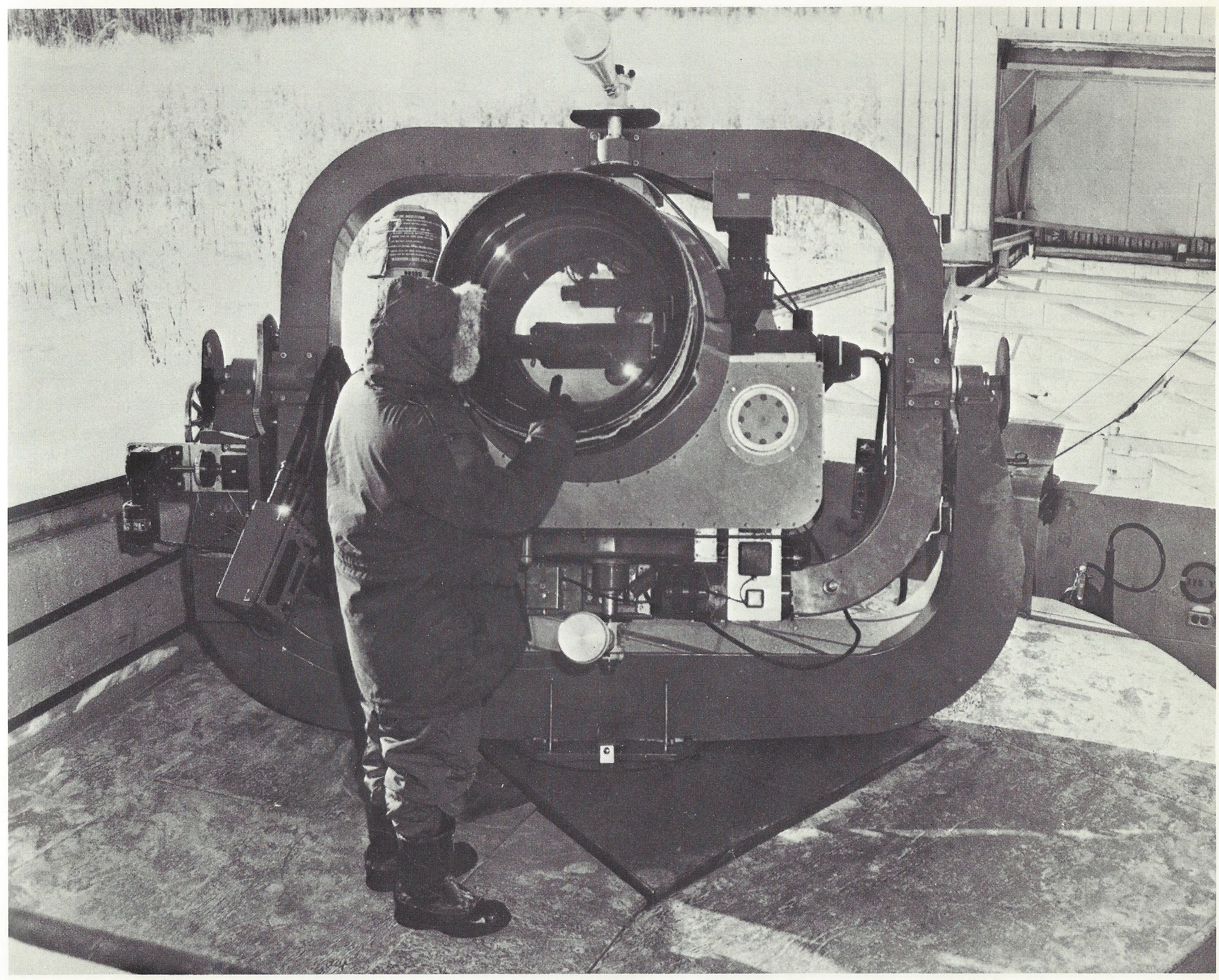 "Caption: ""SPACE BROWNIE - The most sensitive and precise satellite-tracking instrument in NORAD's satellite detection and tracking network is the Baker-Nunn camera, shown here. It can photograph light reflected from an object the size of a basketball out in space about 25,000 miles. This camera, at Cold Lake, Alberta, is operated by the Canadian Forces Air Defense Command. Others supplying data to the NORAD Space Defense Center in Colorado are operated by the U.S. Air Force and the Smithsonian Astrophysical Observatory. By identification and correlation of known star backgrounds in the Baker-Nunn photographs, a satellite's position can be determined with great precision."""