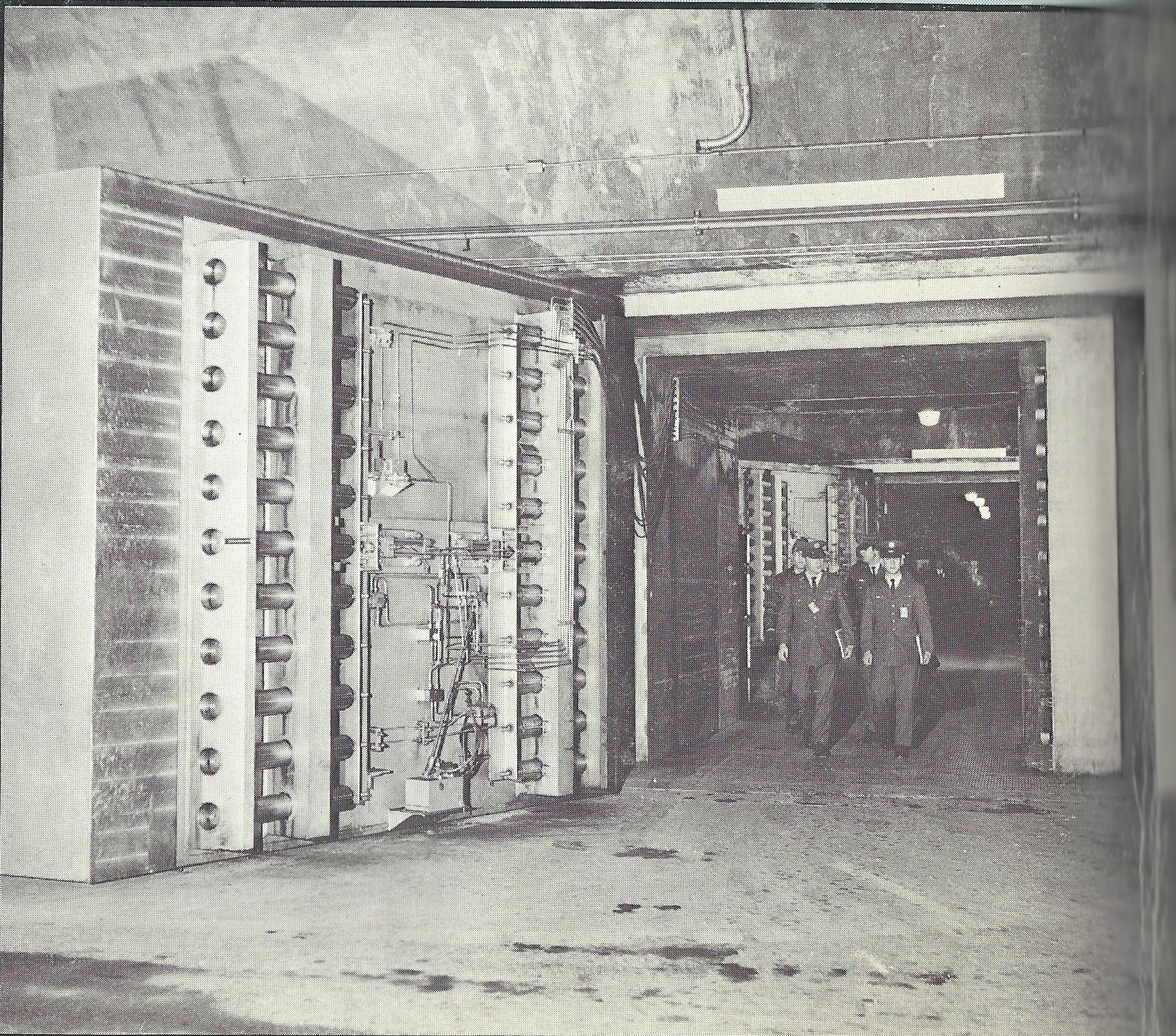 "Caption: ""Operations personnel coming out of the underground NORAD Command Post through one of the 25-ton doors."""