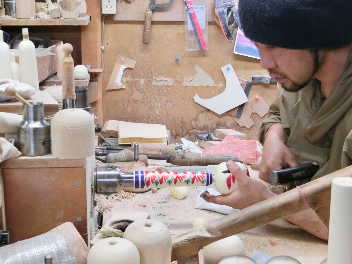 Assemblage de la poupée kokeshi, d'abord par friction, sur le tour, et finition au marteau. / The head is first fixed on the body by friction, with the lathe turning, and then hammered solidly.