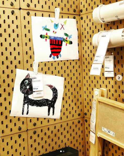 A close up photo of an IKEA display with child-like drawings hanging on a brown peg-board modular wall.