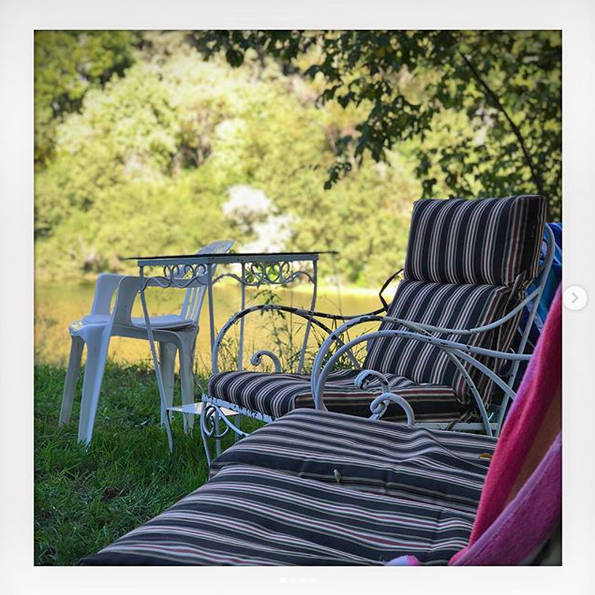 A photo of a number of empty striped lawn chairs outside on a sunny day.