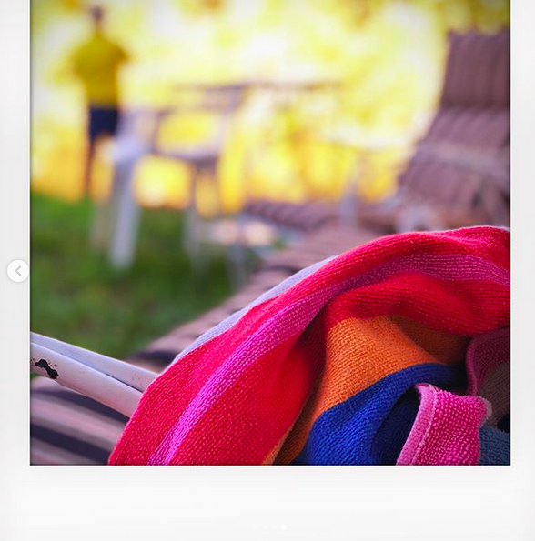 A close up photo of a bright striped beach towel over a lawn chair, with people mingling in the background.