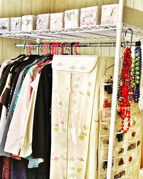 A bright photo of clothes hanging on a clothing rack. There's an assortment of clothes, jewelry,  boxes of shoes, and styles of hangers.