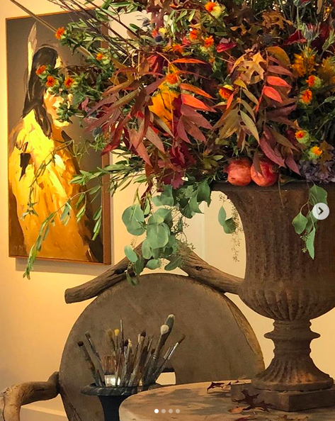 A photograph of the corner of a room with a bouquet of autumnal foliage and flowers in a large stone vase, on a table next to a brown chair, with a jar of paint brushes on it. On the wall behind the flowers is a painting.