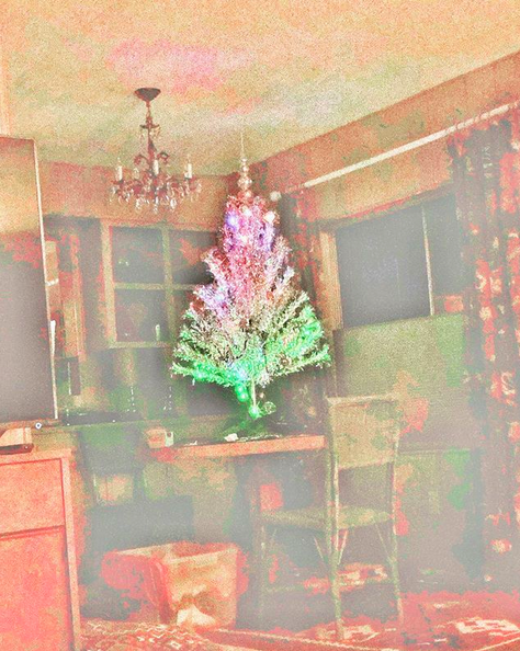 A stylized filtered photo of kitchen with a small Christmas tree on the kitchen table.