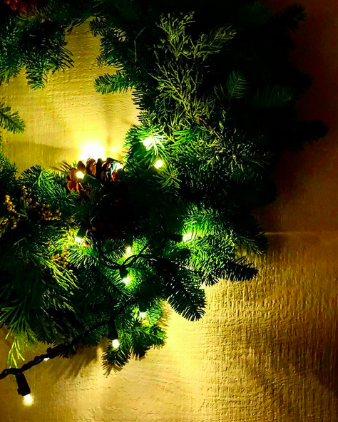 Green evergreen Christmas wreath at night with twinkle lights lit and acorns in it, against a yellow wall.