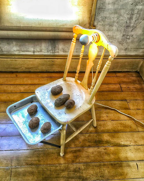 [photo at David Ireland's house on Capp in San Francisco]    Potatoes heating on a wooden chair with a lightbulb and metal tray attached. Organizing gives you space for amazing things!