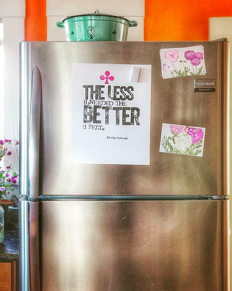 "The front of a stainless steal refrigerator, in a clean kitchen, with art prints on the front. Two pink floral prints, and a quote print that says ""The less I needed, the better I felt."" - Charles Bukowski"