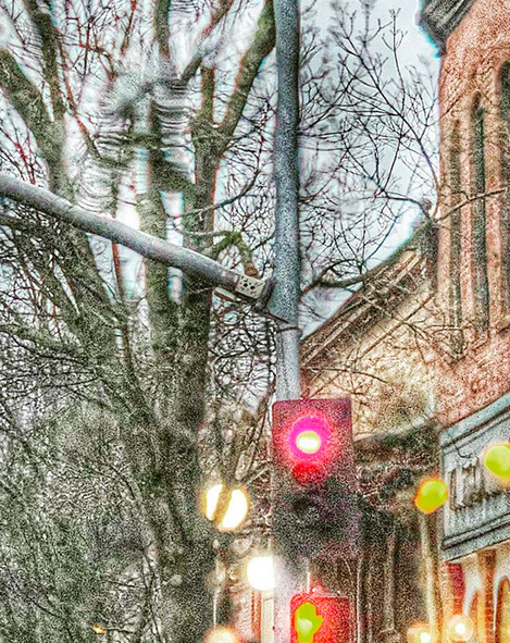 A rainy stop light scene, with bare trees, some shop fronts, and streetlights. Taken driving back from a client's house.