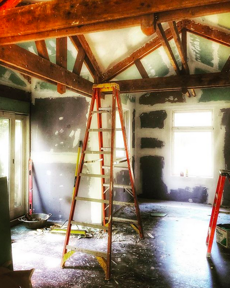 The scene in the middle of refinishing the inside of a cabin in the woods. The wooden ceiling beams are exposed, the ceiling and walls are being touched up and repainted. There are ladders and derby scattered throughout the room.