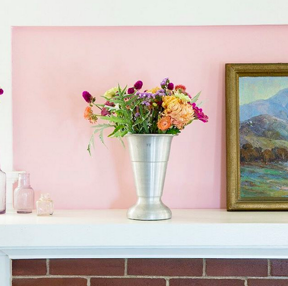 A bright photo of a bouquet of colorful flowers in a silver vase, placed on a fireplace mantle against a pink wall.