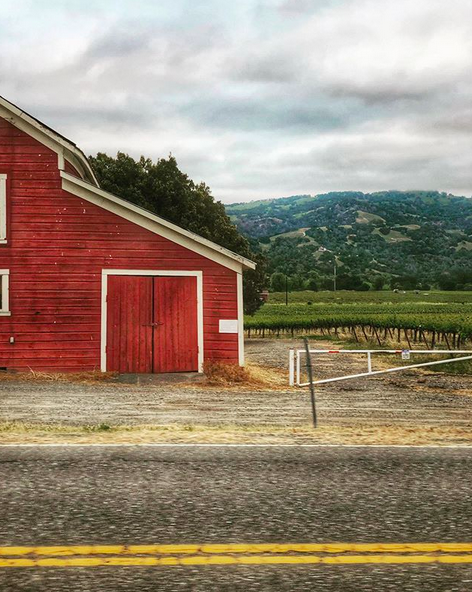 A photo of a bright red barn against a lush green hill, taken from the street as the photographer is driving by.