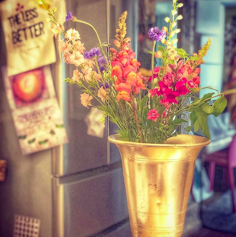 A close up photograph of wildflowers in a gold vase against a kitchen backdrop.