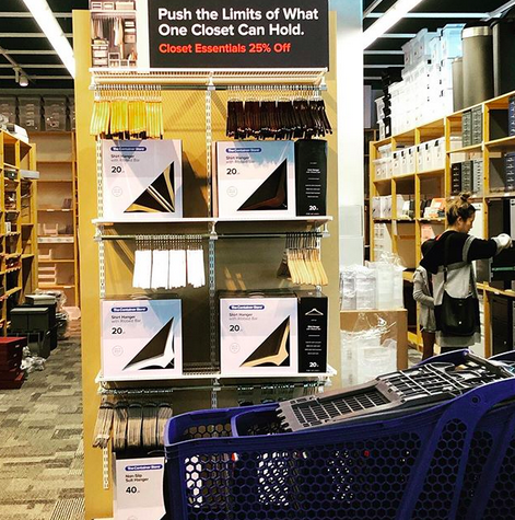 "A crisp photograph of the closet section of the Container Store. With a sign that says ""push the limits of what one closet can hold."""