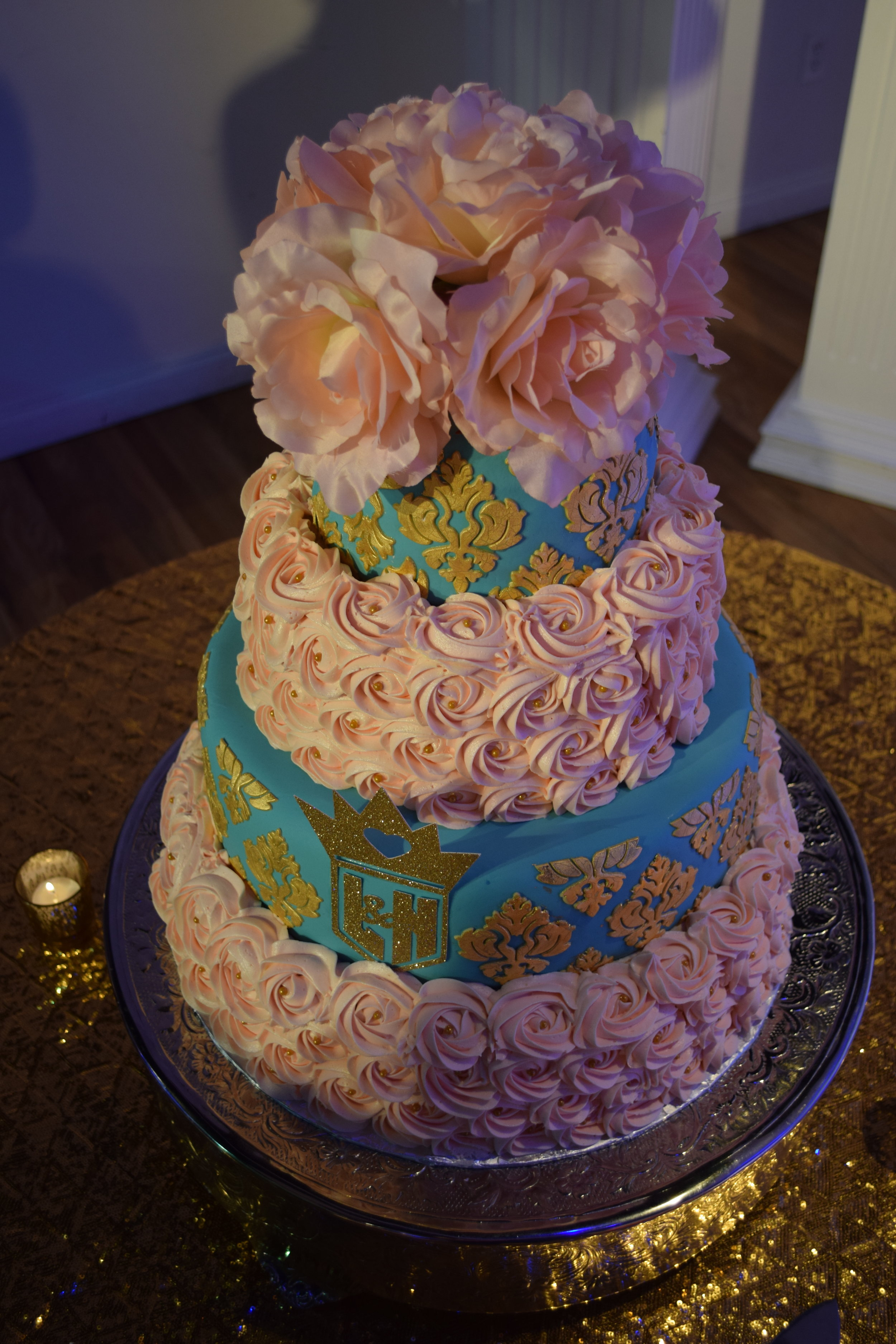 Edible 24 karat Gold Leafing on Fondant Embellishments. Precision Color Matching of buttercream frosting to silk florals on top. Custom cut logo with couples initials.
