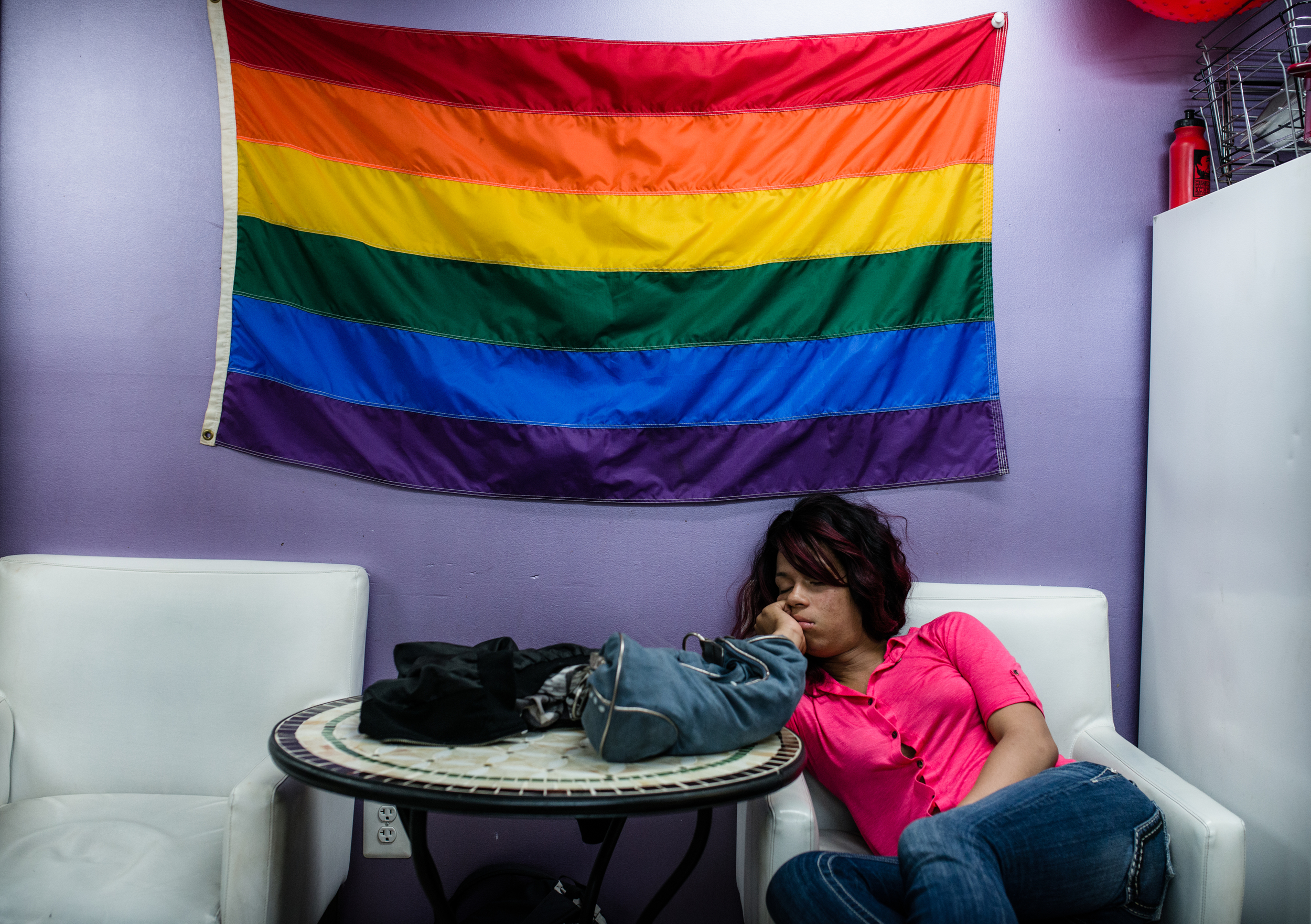 "People take a nap under the LGBT flag inside of Casa Ruby which is the only shelter for transgender group in Washington D.C. May 18th, 2015. ""Casa Ruby was a dream I had many years ago. One time I actually had a dream that I was running a shelter and putting satin sheets on the bed. Now, I'm living my dream. I can serve my community and I can do it in a way that I understand where they're coming from because I'm a member of the LGBT community and I've been homeless."" ――― Shelter owner Ruby Jade Corado"
