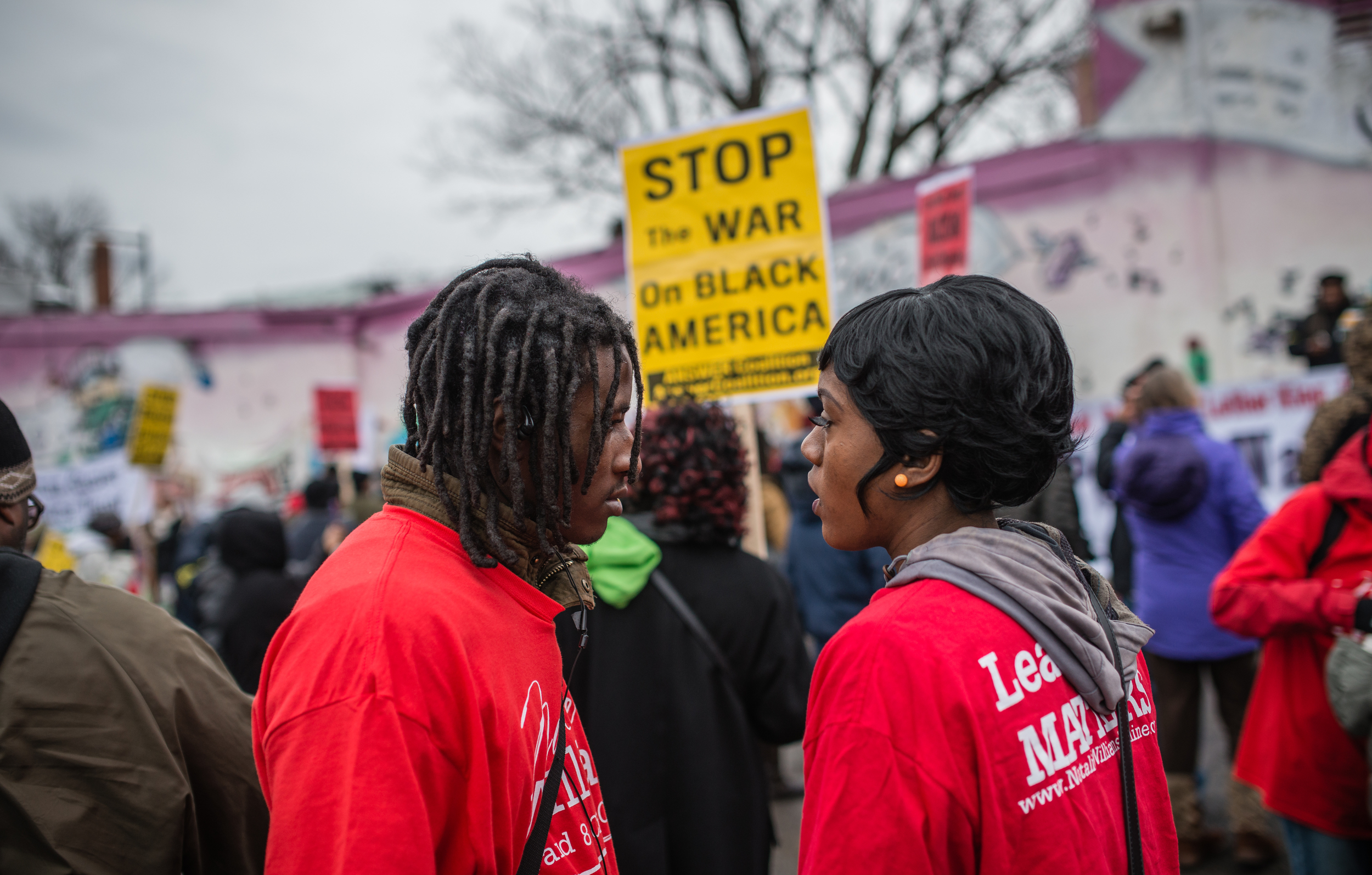 "An African American couple stands in front of a banner ""Stop the War on Black Americans"" during 2015 Martin Luther King peaceful walk parade at southeast Washington, D.C."